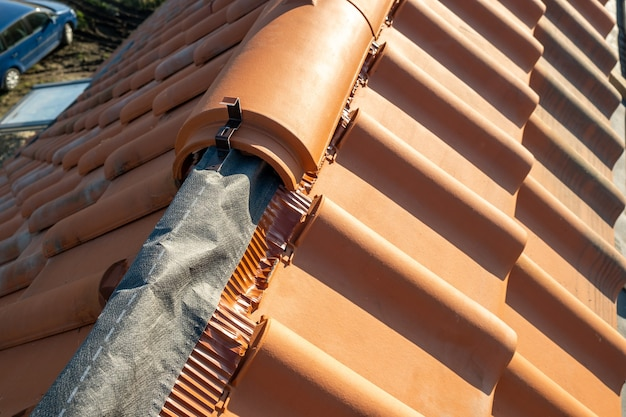 Zbliżenie żółte dachówki ceramiczne kalenicy na dachu budynku mieszkalnego w budowie.