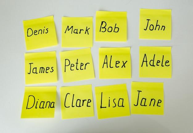 Zbliżenie żółte papierowe naklejki z imionami męskimi i żeńskimi