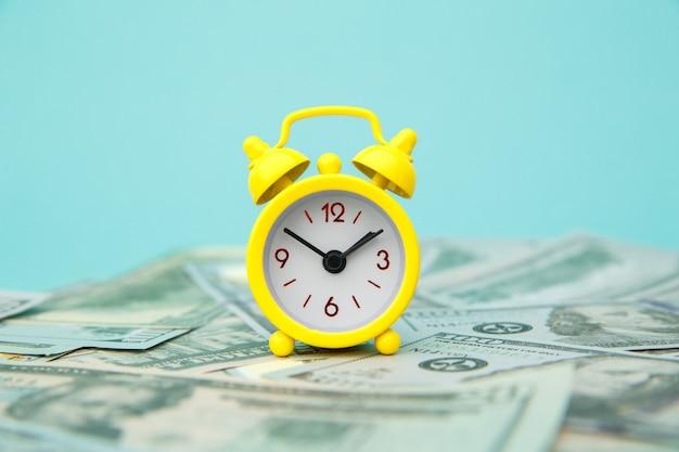 Zbliżenie żółty budzik i pieniądze na niebiesko.