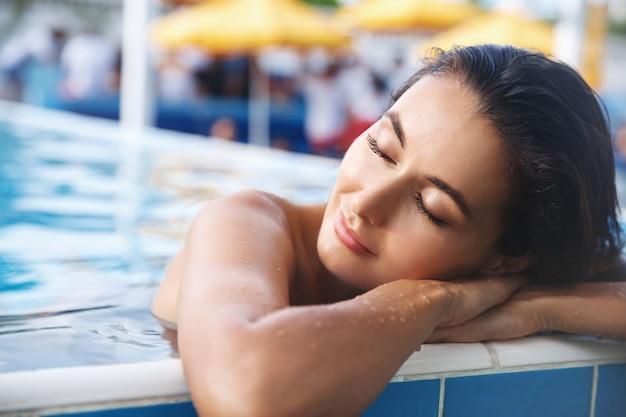 Zbliżenie zrelaksowanej, atrakcyjnej opalonej kobiety, opierającej się o brzeg basenu, uśmiechniętej i zamkniętych oczu.