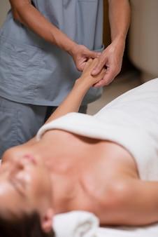 Zbliżenie zrelaksowanej kobiety podczas masażu dłoni
