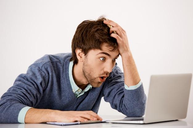 Zbliżenie zszokowanego, niemego młodzieńca siedzącego przy biurku, wpatrującego się w laptopa z wyłupionymi oczami i zdumionego zaskoczonego wyrazu twarzy, czytającego szokujące wiadomości