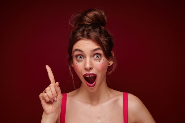 Zbliżenie zszokowanej młodej ładnej brązowowłosej kobiety z przypadkową fryzurą, podnosząc palec wskazujący i patrząc z szeroko otwartymi oczami i ustami, na białym tle