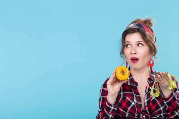 Zbliżenie zszokowany młoda piękna kobieta patrząc na miarkę i trzymając pączek w rękach pozowanie na niebieskim tle z miejsca kopiowania. dieta i odrzucenie szkodliwych wysokokalorycznych pokarmów.