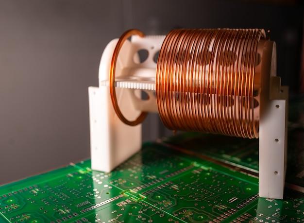Zbliżenie zwoju drutu miedzianego stojącego na dużym mikroukładzie na tle nowoczesnego sprzętu elektronicznego. potężny obwód oscylacyjny i komponenty o wysokiej częstotliwości