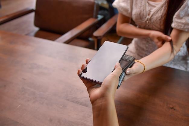 Zbliżeniowa forma płatności. zbliżenie klienta korzystającego ze swojego smartfona i technologii nfs do płatności