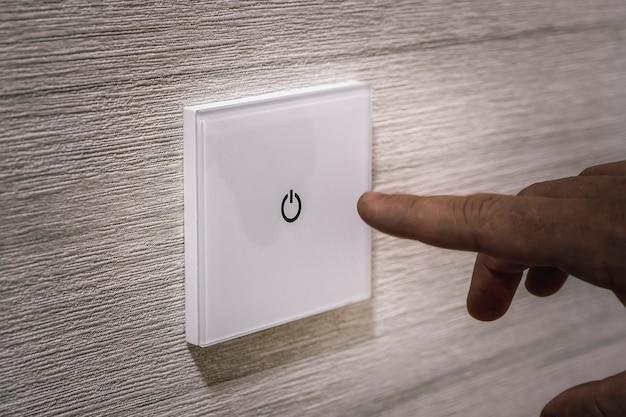 Zbliżony palec włącza światło na przełączniku dotykowym. biały nowoczesny włącznik światła na białej ścianie. nowoczesny design. włączyć wyłączyć