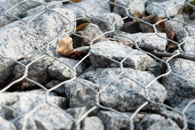 Zbocze zbliżenie kamienia naturalnego pokryte siatką metalową.