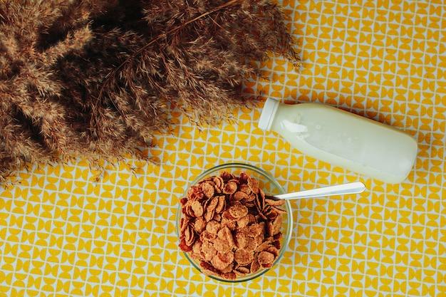 Zboża, łyżka i butelka mleka na stole. zdrowe odżywianie, zdrowe jedzenie na stole.