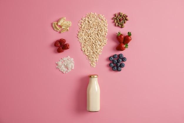 Zboża z suszonymi jabłkami, daktylami, orzechami nerkowca, pistacjami wokół butelki z mlekiem