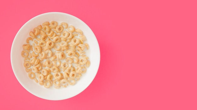 Zboże głęboko z mlekiem w ceramicznej misce na różowym tle