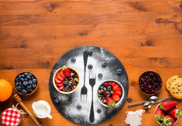 Zboże. śniadanie z musli i świeże owoce w miskach na rustykalnym drewnianym stole