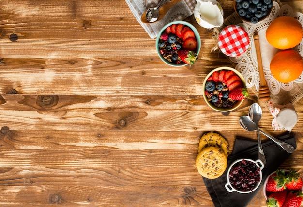 Zboże. śniadanie z musli i świeże owoce w miskach na rustykalnym drewnianym tle,