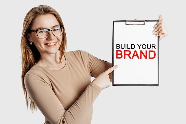 Zbuduj swoją markę. piękna młoda biznesowa kobieta w okularach trzyma schowek z makiety miejsca na białym tle na szarym tle