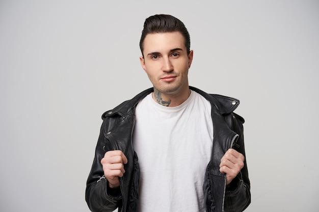 Zbuntowany, atrakcyjny facet ze stylową fryzurą i stylizacją na smar