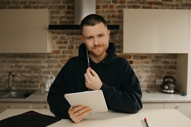 Zdalna nauka online. mężczyzna z brodą studiujący zdalnie na tablecie.