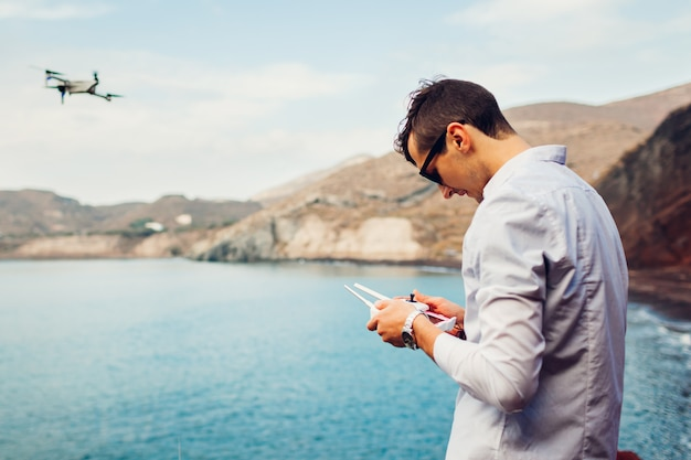 Zdalne sterowanie dronem. mężczyzna operuje kontrolerem helikoptera drogą morską. zdjęcia lotnicze z czerwonej plaży na wyspie santorini