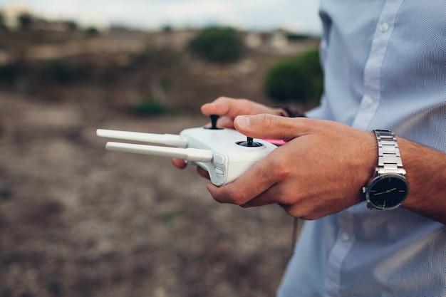 Zdalne sterowanie dronem. mężczyzna trzyma helikopteru kontroler z smartphone. filmowanie z lotu ptaka