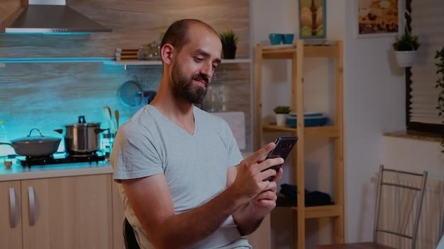 Zdalny pracownik wysyłający sms-y przez telefon podczas pracy w domu późno w nocy. zapracowany, skoncentrowany pracownik korzystający z nowoczesnej technologii bezprzewodowej, wykonujący nadgodziny w celu czytania pracy, pisania, wyszukiwania