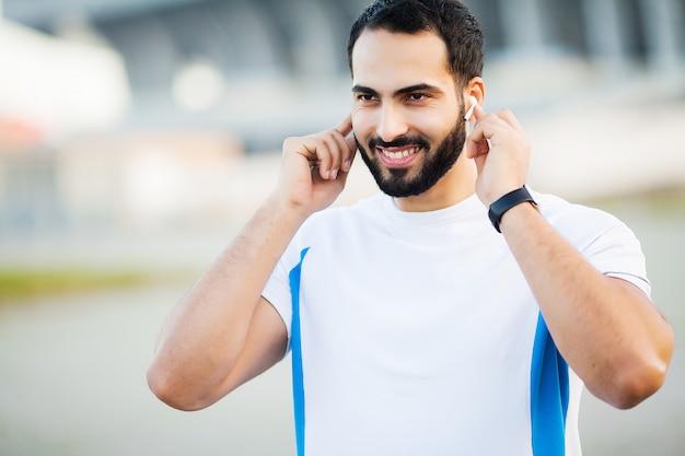 Zdatność. bawi się mężczyzna używa hełmofony dla słuchającej muzyki na ranku biegającym w parku