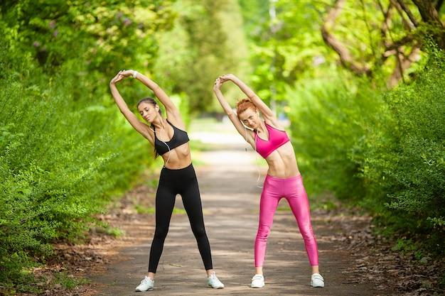 Zdatność. dwa żeńskiego biegacza rozciąga nogi outdoors w parku w lecie