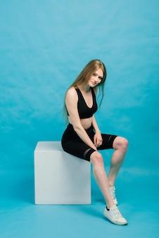 Zdatność. kobieta w odzieży sportowej, rozciągając nogi, rozgrzewając się na niebieskiej przestrzeni.