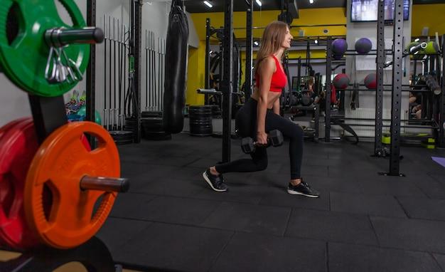 Zdatność. młoda i piękna kobieta pracuje z hantlami w nowoczesnej siłowni. rzuca z hantlami w dłoni