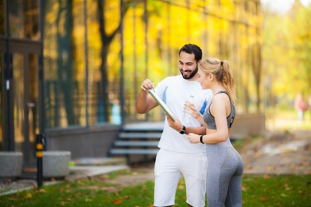 Zdatność. osobisty trener robi notatki, podczas gdy kobieta ćwiczy na wolnym powietrzu