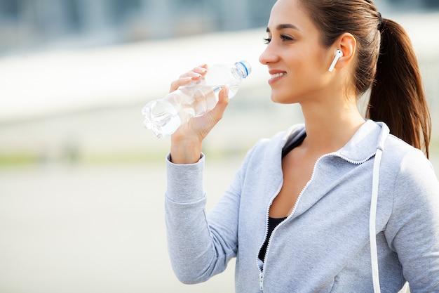 Zdatność. piękna kobiety woda pitna i słucha muzyka po biegać