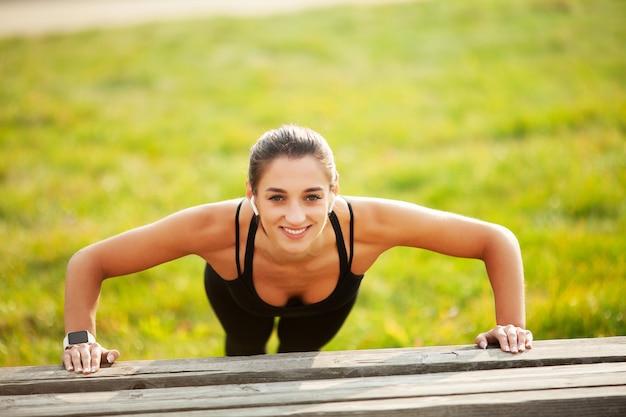 Zdatność. sportowa kobiety pozycja w deski pozyci outdoors przy zmierzchem. pojęcie sportu, rekreacji i motywacji