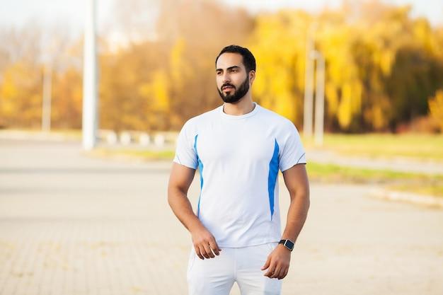 Zdatność. stretch man robi ćwiczenia rozciągające. stojąc do przodu, zginaj odcinki nóg