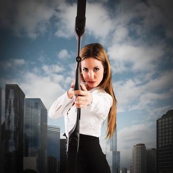 Zdecydowana bizneswoman z łukiem i strzałą