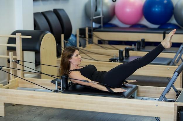 Zdecydowana kobieta ćwicząca ćwiczenia rozciągające na reformatorze