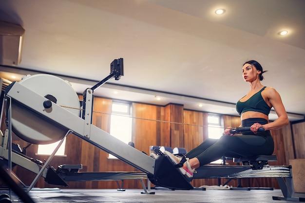 Zdecydowana młoda kobieta pracująca na maszynie w rzędzie w klubie fitness