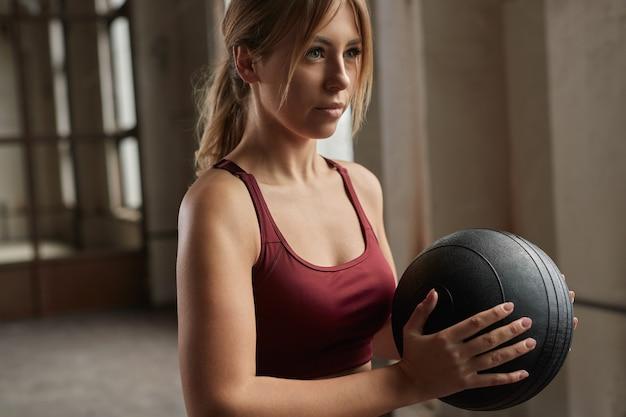 Zdecydowana młoda kobieta z ciężką piłką lekarską w rękach przygotowuje się do ćwiczeń podczas intensywnego treningu funkcjonalnego na siłowni