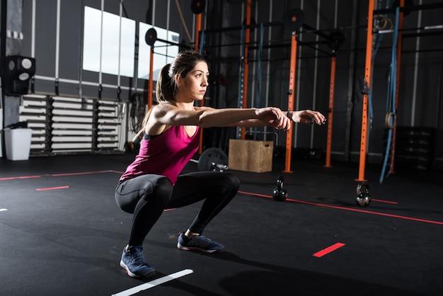 Zdecydowana wysportowana dziewczyna wykonuje ćwiczenia przysiadów na siłowni