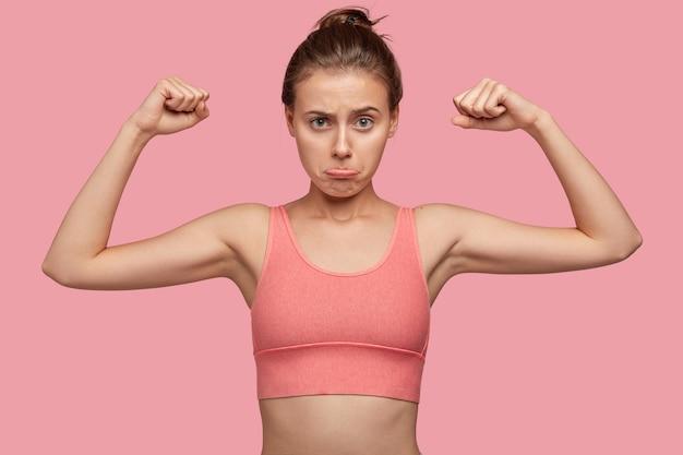 Zdecydowana, wysportowana kobieta o sportowej sylwetce, pokazuje mięśnie, nosi luźny top, zaciska usta