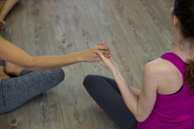 Zdecydowane kobiety ćwiczące ćwiczenia rozciągające na reformatorze