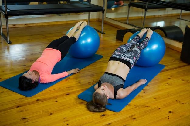 Zdecydowane kobiety ćwiczące z piłką fitness