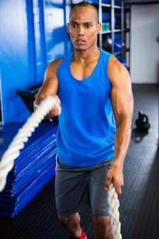 Zdecydowany męski atleta ćwiczy z arkanami