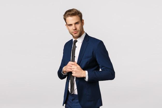 Zdecydowany, pewny siebie biznesmen w garniturze, załatwiający kurtkę, wyglądający pewnie i zadowolony, podpisał dobrą ofertę, czuje się szczęśliwy i pewny siebie, zarządza biznesem