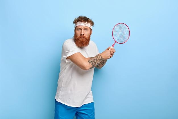 Zdecydowany rudowłosy tenisista trzyma rakietę, pozując przy niebieskiej ścianie