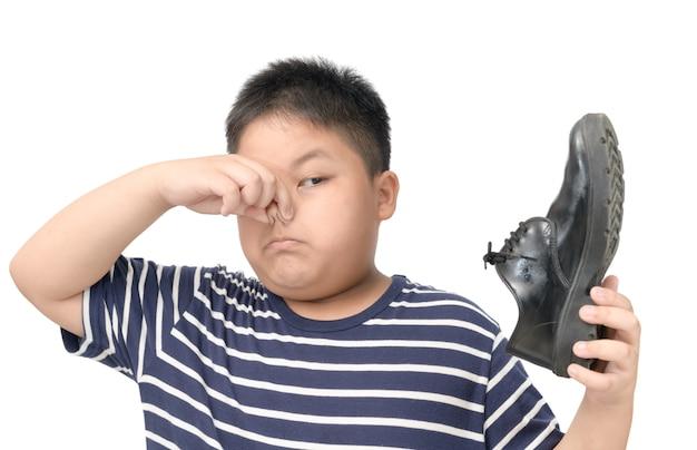 Zdegustowany chłopak trzymający parę śmierdzących skórzanych butów