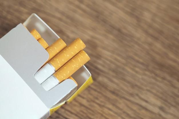 Zdejmij opakowanie papierosów przygotuj do palenia. ustawiono kolejkę do pakowania na drewnianym stole. filtry fotograficzne naturalne światło.