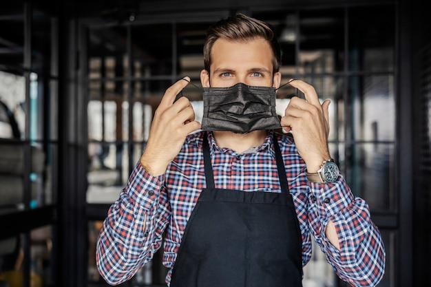 Zdejmowanie lub zakładanie maski na twarz. przystojny kelner o pięknych oczach nosi zegarek na nadgarstku i stoi przy wejściu do restauracji. usługi restauracyjne w czasie koronacji