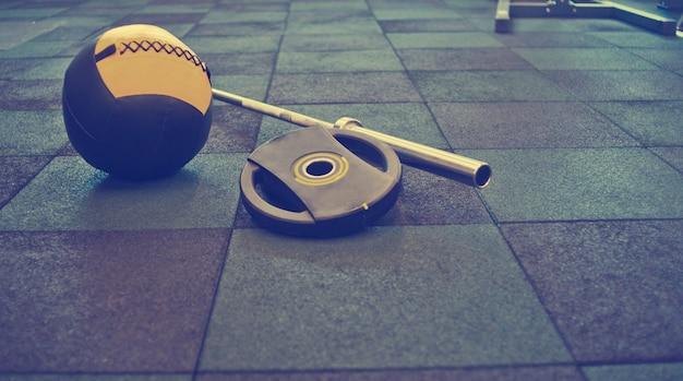 Zdemontowana sztanga, piłka lekarska leżąca na podłodze na siłowni. sprzęt sportowy do treningu z wolnymi ciężarami. trening funkcjonalny