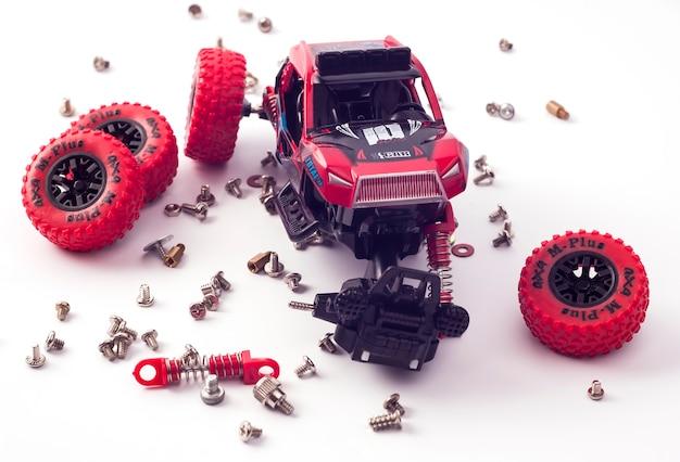Zdemontowany samochód i porozrzucane części. zepsuta zabawka na białym tle