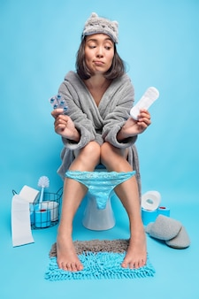 Zdenerwowana azjatka o ciemnych włosach trzyma podpaskę higieniczną i środki przeciwbólowe czuje ból podczas pozaz menstruacyjnych na muszli klozetowej w toalecie nosi maskę do spania wygodne majtki szlafrok na nogach na niebieskim tle