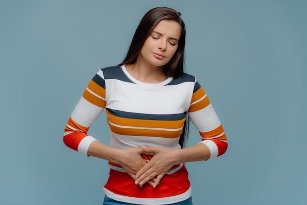 Zdenerwowana brunetka dama źle się czuje, cierpi na bóle brzucha