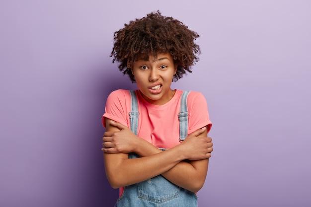 Zdenerwowana ciemnoskóra młoda kobieta ma dreszcze z zimna, ma niezadowolony wyraz twarzy, zaciska zęby